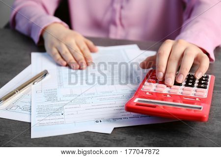 Woman sitting at table with calculator and documents