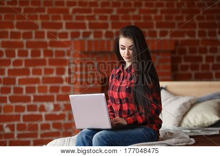 Pretty woman relaxing on the bed in her room and chatting on her laptop. Indoors. Online friendship and social network concept