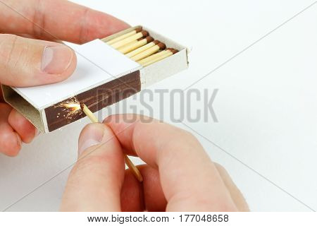 Closeup Outdoor White Boxes Of Matches. Hands Strike A Match On The Boxes. Isolated On White Backgro