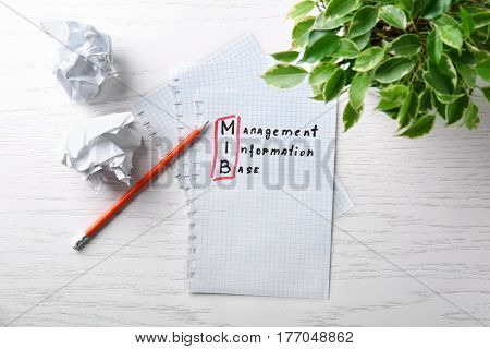 Management concept. Notepad, pencil and houseplant on white wooden table