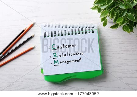 Management concept. Notepad, pencils and houseplant on white wooden table