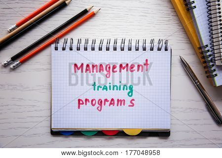Notebook with written text MANAGEMENT TRAINING PROGRAMS on wooden background
