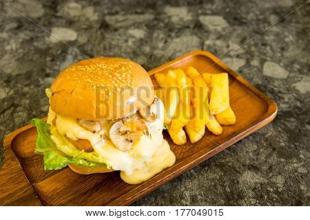 Cream mushroom sauce Burger with French fries on wood plate.