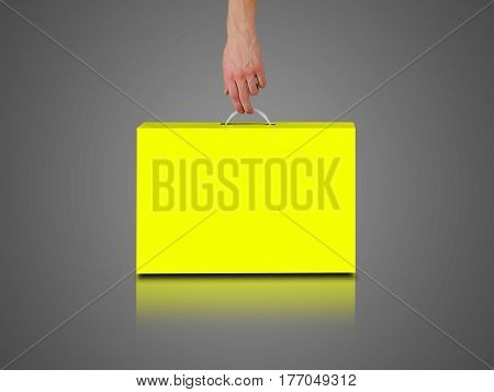 Hand Holds A Yellow Box With A Handle. Packing Box For Laptop. Isolated On Grey Background