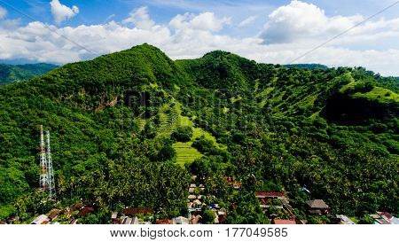 Aerial landscape view of green mountains and blue sky with clouds at village Candidasa Bali Indonesia.