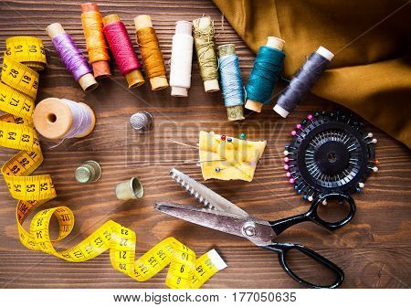 Scissor, Buttons, Zip, Tape Measure, Thread And Thimble On Fabrics On Dark Wooden Background, Flat L