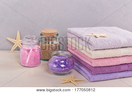 Stack of colorful bath towels with sea salt on light background. Pastel colors cotton towels. Hygiene fabricspa and textile concept