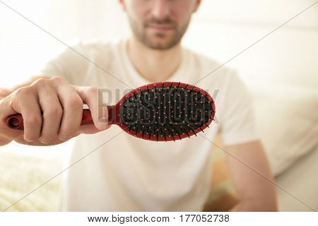 Hair loss concept. Young man with hair comb, closeup
