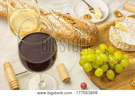 A photo of a wine and cheese tasting, with bread, grapes, and glasses of red and white wine