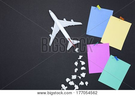 Airplane model with various paper ball and blank colorful paper note on black background with copy space.Preparation for Traveling and tour concept