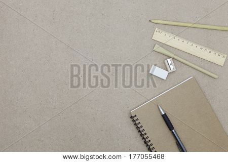 Notebook with pen and pencil eraser on brown paper background