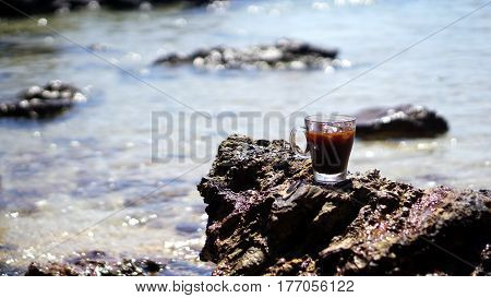 A glass of ice coffee on the beach