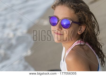 Smiling girl sunbathing on the beach after bathing.