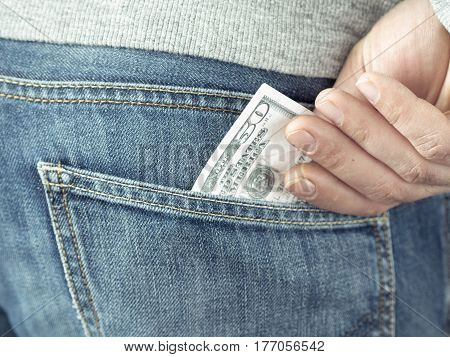 his hand put dollars in jeans pocket or take out from pocket