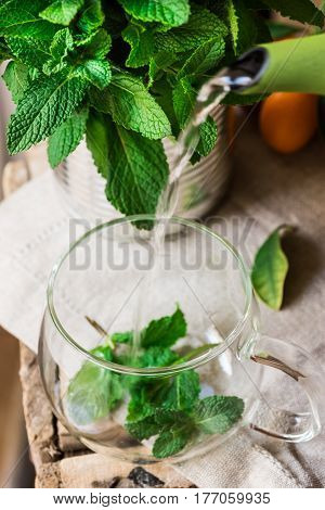 Pouring hot splashing water from pot into glass cup brewing fresh mint herbal tea linen cloth kinfolk top view