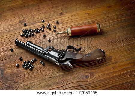 percussion pistol revolver on the wooden table still life with powder box and lead