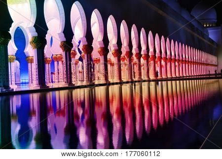 The grand mosque in Abu Dhabi lit up beautifully with colorful lights at night.