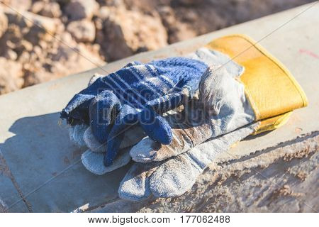 Leather gloves with blank gloves on top. All placed on a concrete pole during a sunny shine to shine.
