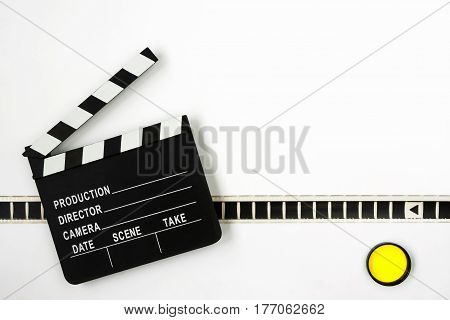 Clapperboard yellow color filter and film lie on a white background