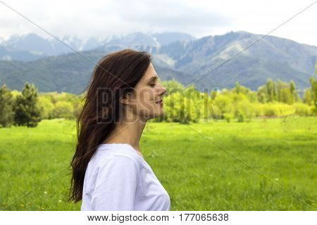 profile of young woman with eyes closed breathing fresh air in the mountains.