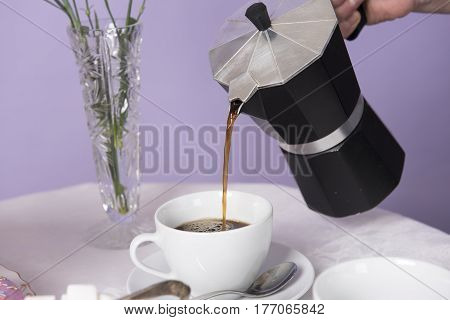 An unrecognisable hand pouring a cup of coffee in a white mug.