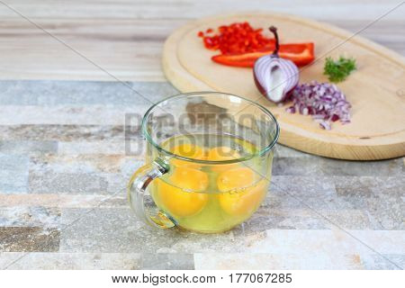 Making egg omelette with cut onion red pepper and garden cress