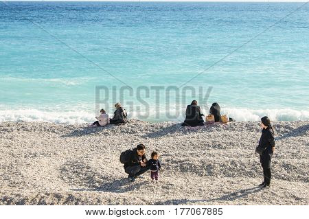 Nice, France - 25 February, Tourists at the water's edge, 25 February, 2017. People and tourists having a rest on the Cote d'Azur.
