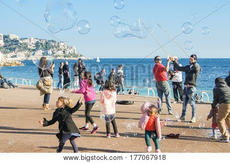 Nice, France - 25 February, Children catch soap bubbles, 25 February, 2017. People and tourists having a rest on the Cote d'Azur.