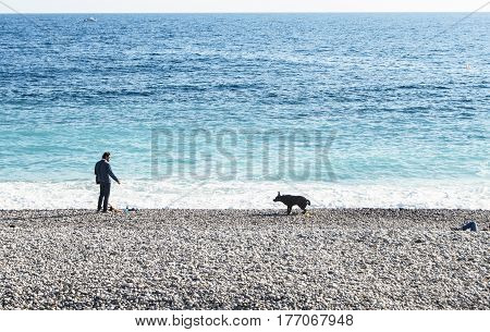 Nice, France - 25 February, A man and a dog on the shore, 25 February, 2017. People and tourists having a rest on the Cote d'Azur.