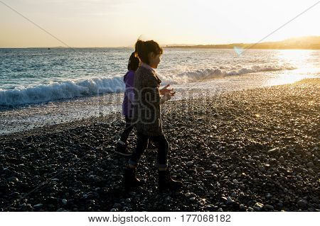 Nice, France - 25 February, Teenagers by the sea at sunset, 25 February, 2017. People and tourists having a rest on the Cote d'Azur.