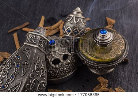 Silver Oriental Artisitc Arabian Oud Perfume / Arabian Oud Perfume with Oud Scented Wood burned in the background with Scented Smoke in the Air