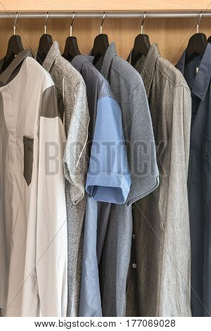 Clothes Hanging On Rail In Wooden Wardrobe