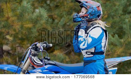 Girl Bike wears a helmet - MX moto cross racing - rider on a dirt motorcycle, telephoto