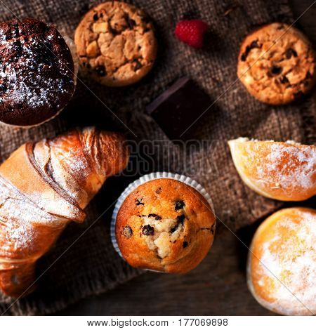 Delicious Chocolate muffins croissants and dark chocolate pieces on wooden table - Food background