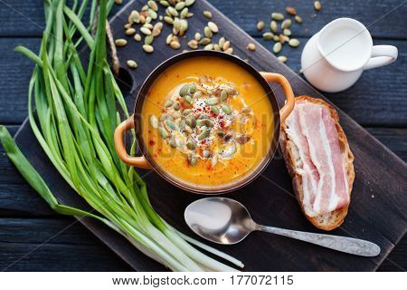 Homemade pumpkin soup with cream, bread, bacon and pumpkin seeds on a wooden background. Top view.