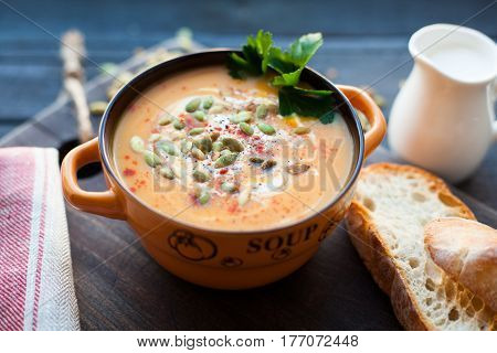 Homemade pumpkin soup with cream, bread, greens and pumpkin seeds on a wooden background. Top view.