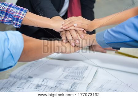 Close up group of Construction engineerworkerforeman and owner shake up their hand after achieve their mission or construction.