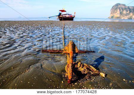 Steel pillar with rope parking boat during low tide with sand and blue sky (Focus Steel pillar) .