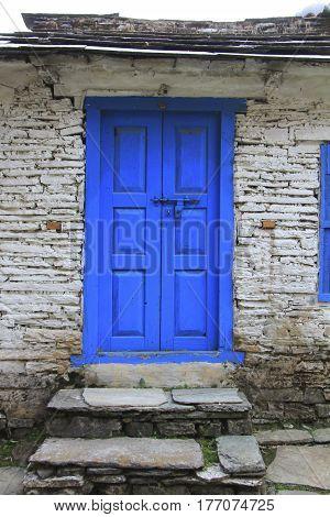 Grunge gray bricks wall with blue door of Nepali house