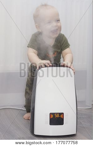 Baby boy staying leaning against the humidifier. Laughing and smiling lovely toddler.