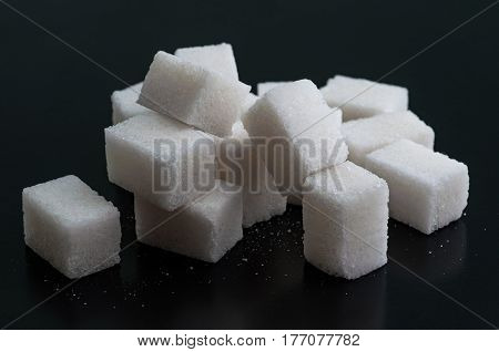 The white granulated sugar isolated on black