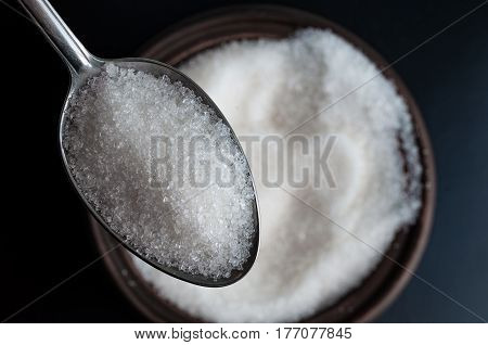 a spoon full of white sugar. sugar in spoon over a bowl full of sugar