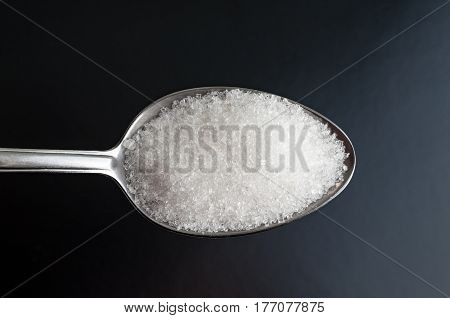 A spoon with white sugar on black background. Closeup studio photography