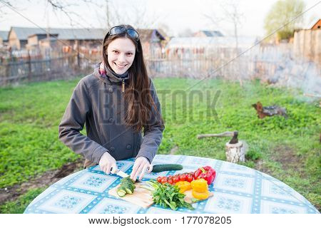 Happy young woman cutting fresh vegetables on a table outside in the garden
