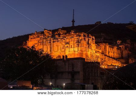 Glowing Cityscape At Bundi At Dusk. The Majestic Fort Perched On Top Dominating The Town. Scenic Tra