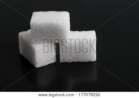 The White cubes sugar on black background.