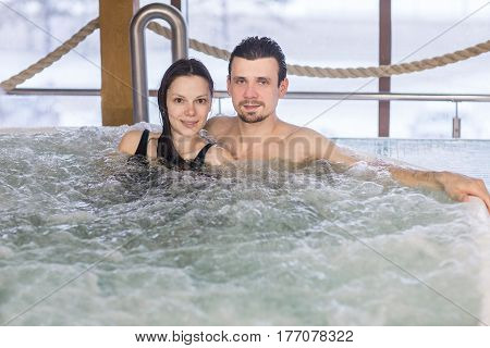 Couple in love relax in a bath with hydro massage in Spa salon