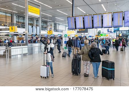 AMSTERDAM THE NETHERLANDS - MAY 16 2016: Travellers and waving woman with headscarf at Schiphol Airport near Amsterdam in The Netherlands