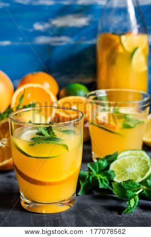 Refreshing beverage citrus lemonade oranges lime fresh mint in bottle and glasses sliced fruits on wood table blue background by window