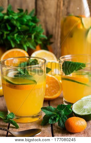 Refreshing citrus lemonade from lime oranges fresh mint in glasses and bottle sliced scattered fruits wood kitchen table by window close up